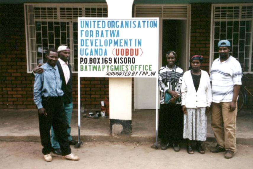 Five staff members of United Organisation for Batwa Development in Uganda (UOBDU) stand beside their new office